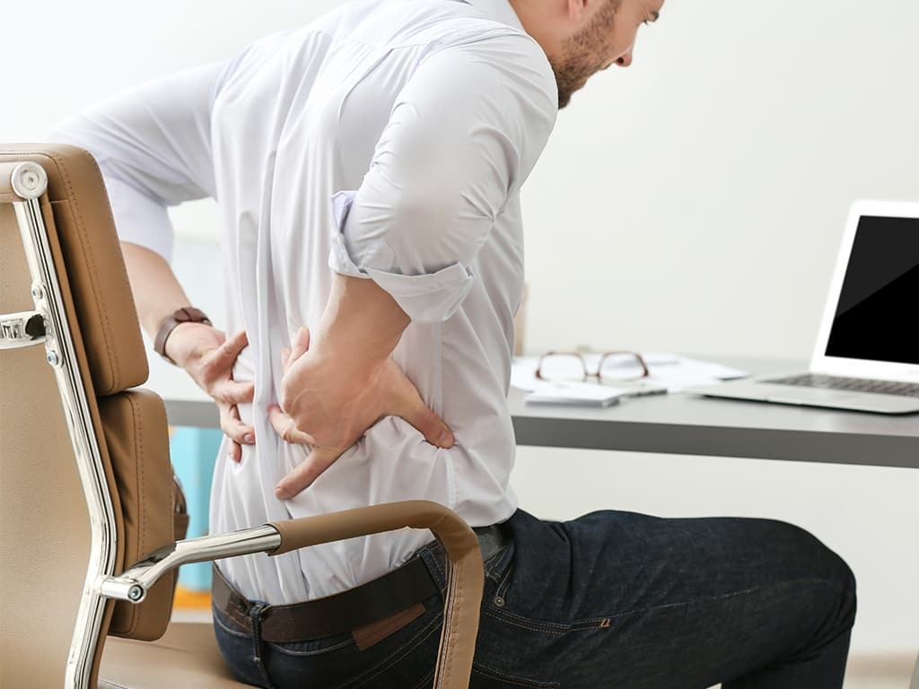 Man sitting at desk with back pain