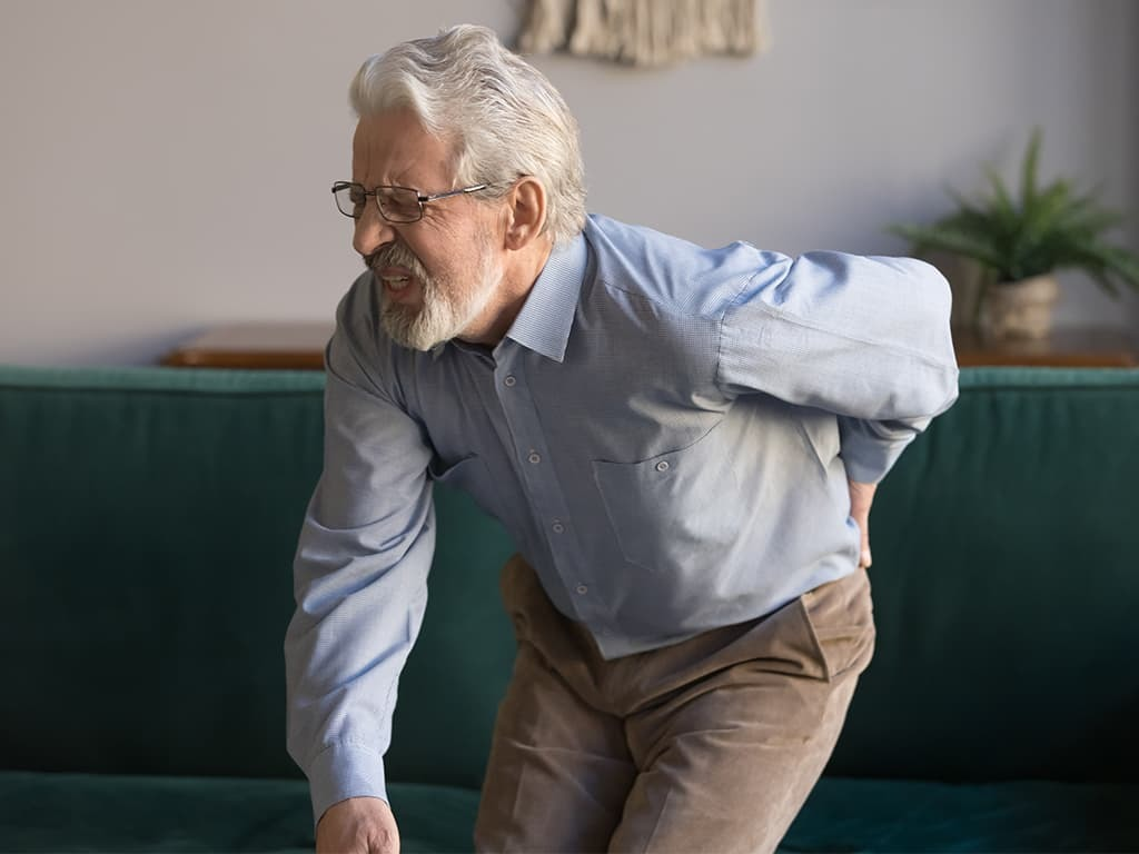 Old man suffering from degenerative disc disease